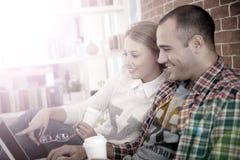 Roomates a casa su un sofà che guarda un video Fotografia Stock