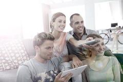 Roomates regardant la TV et à l'aide du comprimé Images stock