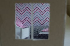 Roombox girl`s room on a smaller scale. Doll furniture in scale 1:24. Rumboks bedroom girls in gray-pink colors. Close-up view through the window royalty free stock images