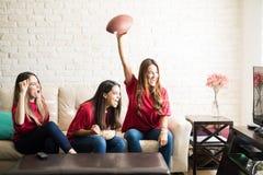 Roomies che guarda una partita di football americano fotografia stock libera da diritti