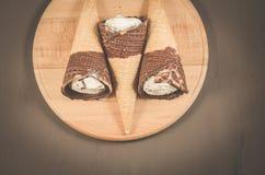 roomijs drie met kegel in roomijs chocolade/drie met kegel in chocolade op een ronde houten steun, hoogste mening stock foto