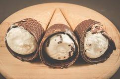 roomijs drie met kegel in roomijs chocolade/drie met kegel in chocolade op een ronde houten steun, selectieve nadruk stock foto