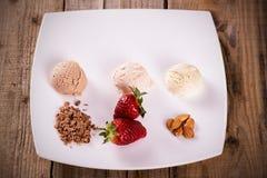 Roomijs met aardbeien, chocolade en amandelen stock afbeeldingen