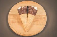 Roomijs twee met kegel in chocolade op een rond houten roomijs steun/twee met kegel in chocolade op een ronde houten steun bovenk stock fotografie