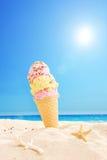 Roomijs in zand op een zonnig tropisch strand wordt geplakt dat Royalty-vrije Stock Foto