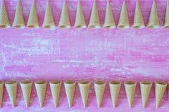 Roomijskegels op roze houten achtergrond stock afbeeldingen