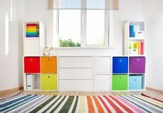 Rooom colorido de los niños con las paredes y los muebles blancos imagenes de archivo