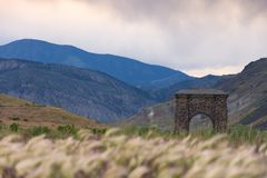 Roosevelt Arch. At the North Entrance of Yellowstone National Park with tall grass in the foreground and mountains behind. Dramatic clouds hang over the valley Royalty Free Stock Images
