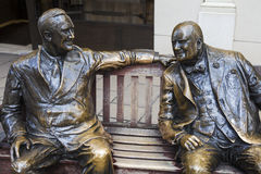 Roosevelt and Churchill Statues in London. Statues of iconic wartime leaders Franklin D Roosevelt and Winston Churchill both sitting on a bench on Bond Street in Royalty Free Stock Image
