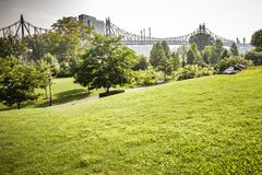 Roosevelt Island park with NYC in background. Beautiful Roosevelt Island park with Manhattan, New York City and Queensboro bridge in background during sunny royalty free stock images