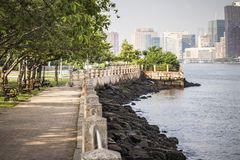 Roosevelt Island park with NYC in background. Beautiful Roosevelt Island park with Manhattan, New York City in background during sunny summer day stock photos