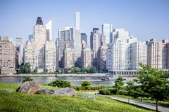 Roosevelt Island park with NYC in background. Beautiful Roosevelt Island park with Manhattan, New York City in background during sunny summer day royalty free stock photo
