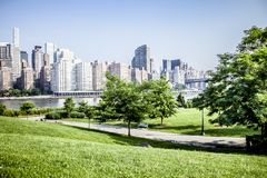 Roosevelt Island park with NYC in background. Beautiful Roosevelt Island park with Manhattan, New York City in background during sunny summer day royalty free stock photography