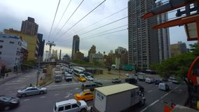 Roosevelt Island Tram Manhattan, New York City. Time-lapse) Mid-day traffic enters Manhattan from Queens on the Queensboro Bridge as the Roosevelt Island Tram stock video footage
