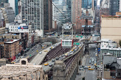 Roosevelt Island Tramway. NEW YORK, USA - MARCH 16:  View on the Roosevelt Island Tramway, hanging in the air above the road and beginning of the bridge and Royalty Free Stock Photography