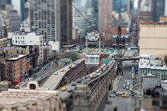 Roosevelt Island Tramway. Tilt-shift view on the Roosevelt Island Tramway, hanging in the air above the road and beginning of the bridge and transporting Royalty Free Stock Images