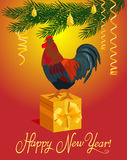 Rooster and gift under the Christmas tree. Stock Image