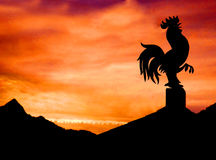 Rooster weather vane. View of the silhouetted Alps mountain range against a sunset sky. Cock/rooster weather vane silhouetted in the foreground royalty free stock photo