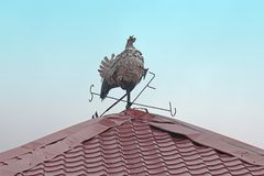 Weather vane rooster on roof top. Rooster weather vane figurine on top of the roof with blue sky in the background royalty free stock photography