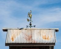 Rooster weather vane pointing west on top of tin roof. An old fashion rooster weather vane on top of hot tin roof pointing west stock photos