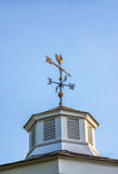 Rooster weather vane on a rooftop with an arrow and North-South Royalty Free Stock Photos