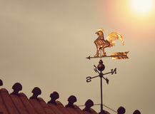 Rooster weather vane on sunset. Golden reflection stock images