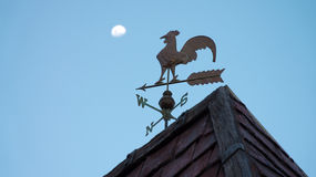 Rooster Weather or Wind Vane. A rooster weather or wind vane on top of a roof with the moon and blue sky in the background. Photo taken on: August 17th, 2013 Stock Photography