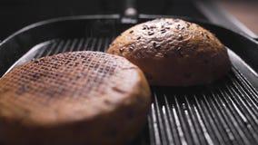 Roosterend knapperige broodjes voor burgers, die hamburger maken, wordt het snelle voedsel, die broodjes geroosterd thuis koken stock video