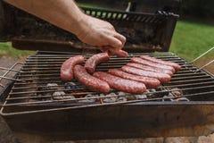 Roosterend worsten bij barbecue de grill openlucht stock afbeeldingen