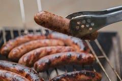 Roosterend worsten bij barbecue de grill openlucht royalty-vrije stock afbeelding