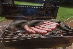 Roosterend worsten bij barbecue de grill openlucht stock afbeelding