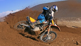Roosting Dirt. Dirt Bike Racer Competing at a Desert Race roosting dirt out of a corner Stock Photo