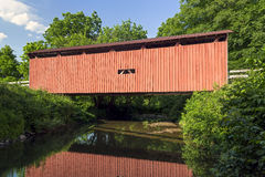Root Covered Bridge Reflection. Built in 1878, the historic red Root Covered Bridge, is reflected in the waters of the West Branch of the Little Hocking River in Stock Photo