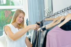 Rooting through clothes rack for bargain. Rooting through a clothes rack for a bargain Royalty Free Stock Photos