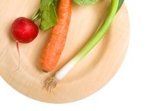Roots on Bamboo. Radish, carrot and scallion on an environmentally friendly bamboo plate Stock Photography
