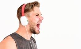 Rop och skrika kopiera avst?nd lyssnande musik för orakad man i hörlurar med mikrofon sexig muskulös man att lyssna sportmusik ma royaltyfria bilder