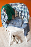Ropa adolescente en una silla Imagenes de archivo