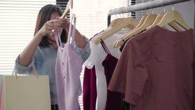 Ropa asiática de las compras de la mujer Comprador que mira la ropa en el carril dentro en tienda de ropa almacen de video