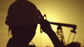 Ropa blanca del casco y de trabajo del ingeniero de la mujer de la silueta que lleva en la puesta del sol Industrial, concepto de metrajes