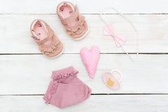 Ropa, calzado y accesorios para el bebé en una madera blanca Imagenes de archivo