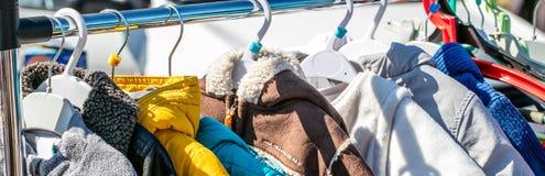 Ropa, chaquetas usadas y capas del invierno del bebé exhibidas en el estante Foto de archivo libre de regalías