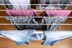 Ropa colgada en el secador de ropa dentro imagenes de archivo