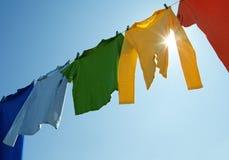 Ropa colorida en una línea y un sol del lavadero que brillan Imagen de archivo libre de regalías