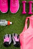 Ropa de deportes, accesorios y zapatos rosados, para la aptitud, una botella de agua, en el fondo de la hierba Imágenes de archivo libres de regalías