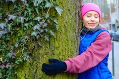 Ropa de deportes que lleva de la mujer que abraza el árbol Foto de archivo