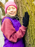 Ropa de deportes que lleva de la mujer que abraza el árbol Imagen de archivo libre de regalías