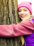 Ropa de deportes que lleva de la mujer que abraza el árbol Fotos de archivo