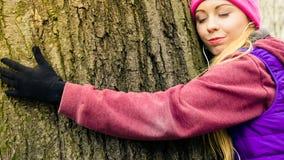 Ropa de deportes que lleva de la mujer que abraza el árbol Fotos de archivo libres de regalías