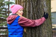 Ropa de deportes que lleva de la mujer que abraza el árbol Foto de archivo libre de regalías