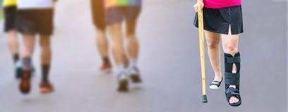 Ropa de deportes que lleva de la mujer de lesión con la tablilla negra de la pierna que coloca a foto de archivo